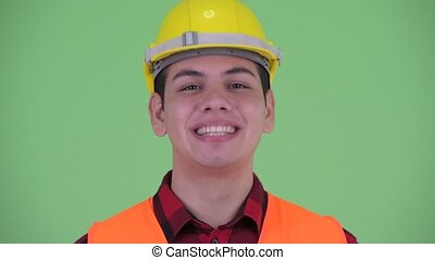 Happy young multi ethnic man construction worker nodding...