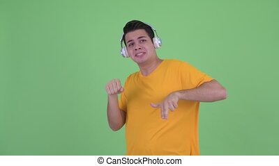 Happy young multi ethnic man listening to music and dancing
