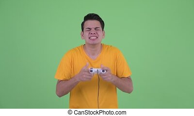Happy young multi ethnic man playing games and winning