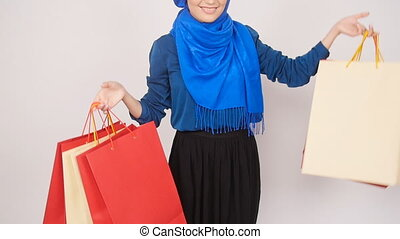 Happy young Muslim woman is carrying shopping bag. - Happy...