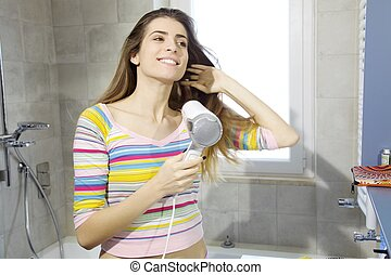 Happy young natural woman  drying hair in bathroom