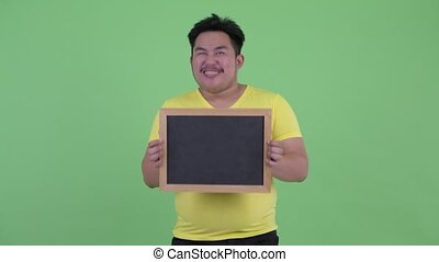 Happy young overweight Asian man holding blackboard