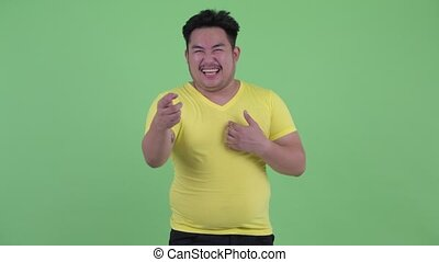 Happy young overweight Asian man laughing and pointing at...