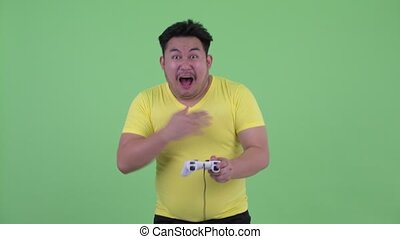 Happy young overweight Asian man playing games and winning