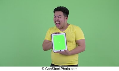 Happy young overweight Asian man showing digital tablet and looking surprised