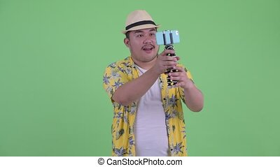 Happy young overweight Asian tourist man vlogging and...