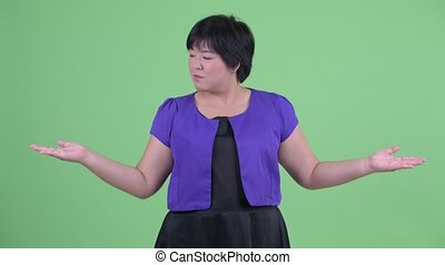 Happy young overweight Asian woman comparing something -...