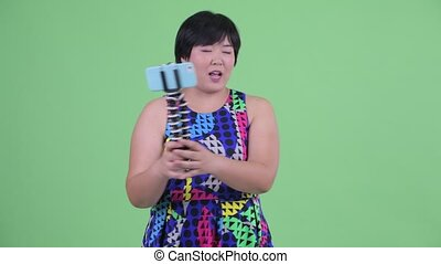 Happy young overweight Asian woman vlogging and showing...