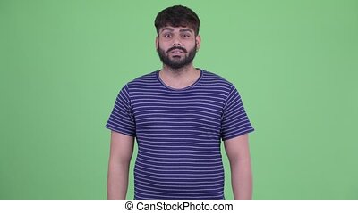 Happy young overweight bearded Indian man talking - Studio...