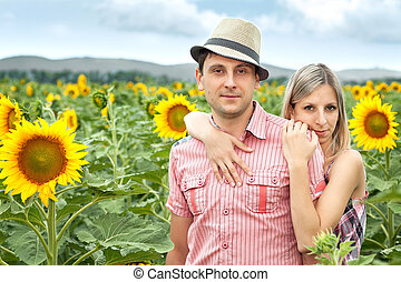 happy young pair in sunflowers