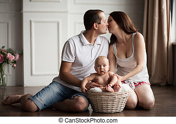 Happy young parents close to small baby in wicker basket.