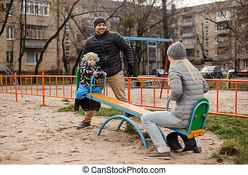 Happy young parents having fun with a little son