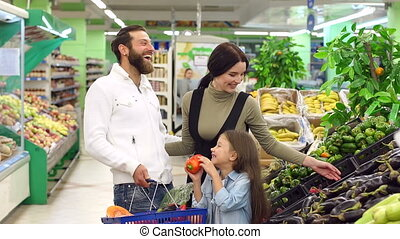 Happy young parents make purchases with their daughter in the supermarket.
