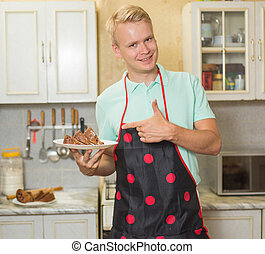 happy young pastry chef, a man proudly holds cooked pie