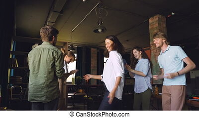 Happy young people are dancing in circle at office party, clapping hands and laughing enjoying corporate holiday. Men and women are wearing casual clothing.