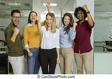 Happy young people are standing in a modern office