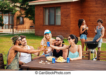 Happy young people celebrating and drinking outdoors
