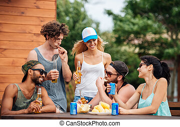 Happy young people eating and drinking outdoors
