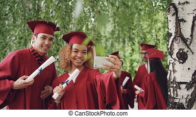 Happy young people girl and guy are taking selfie after...