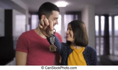 Happy young people holding keys to new home