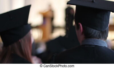 """Happy young people in academic caps with tassels talking at graduation ceremony"""