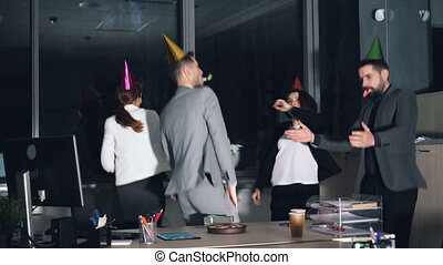 Happy young people office workers are dancing at company party wearing party hats and blowing horns. Birthday cake and gift box are visible on desk.