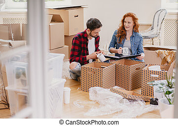 Happy young people packing stuff into boxes while moving out from home