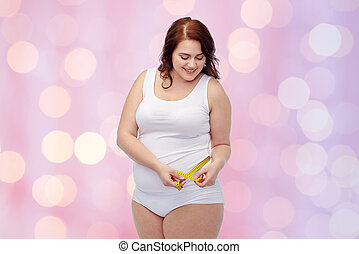 happy young plus size woman with measuring tape - weight...