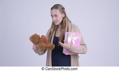 Happy young pregnant woman getting teddy bear and gift box as presents