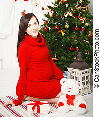 Happy young pregnant woman near the Christmas tree