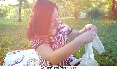 Happy young pregnant woman playing with baby sweater