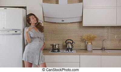 Happy young pregnant woman preparing meal, girl cooking ...