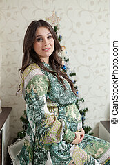 Happy young pregnant woman sitting near the Christmas tree