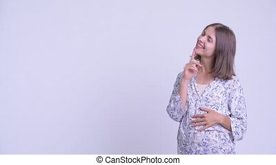 Happy young pregnant woman thinking while pointing up -...