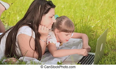 Happy young pretty sisters working on laptop at morning