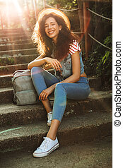 Happy young pretty woman sitting on steps