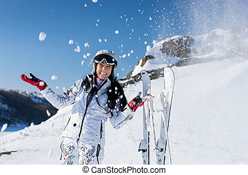 Happy young skier tossing snow in the air