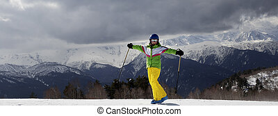 Happy young skier with ski poles in sun mountains and cloudy gray sky before storm