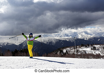 Happy young skier with ski poles in sun mountains and cloudy gray sky