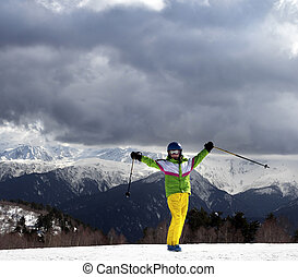 Happy young skier with ski poles in sun mountains