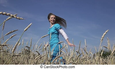 happy young slender woman with a long fair hair in a blue...