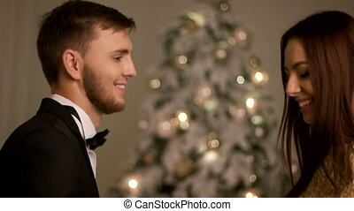 Happy young smiling couple having fun on a Christmas party and dancing near the xmas tree.