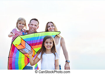 Happy young smiling family with flying a kite on the beach