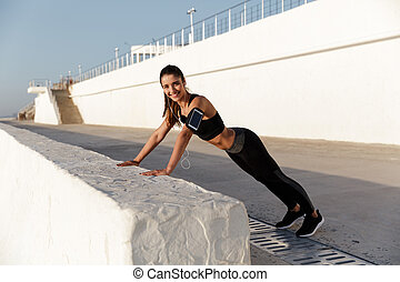 Happy young sports woman listening music make sport exercises.