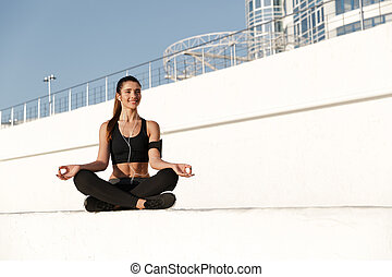 Happy young sports woman listening music make yoga exercises.