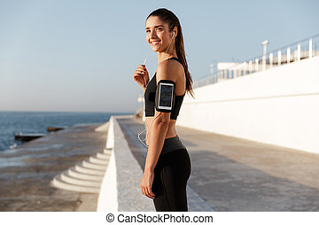 Happy young sports woman listening music outdoors.