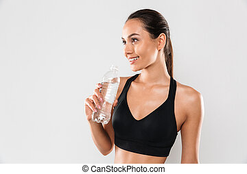 Happy young sports woman posing isolated drinking water.