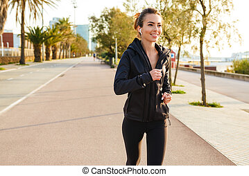 Happy young sports woman running