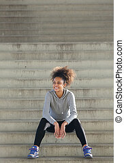Happy young sports woman sitting on steps outdoors