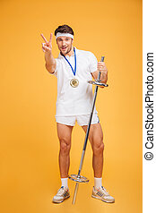 Happy young sportsman with barbell standing and showing victory sign